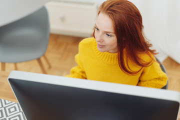 Young redhead woman working at a desktop monitor