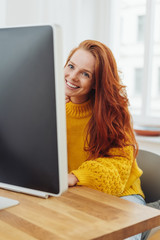 pretty young redhead woman working at a desktop