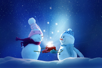 Wall Mural - Merry christmas and happy new year greeting card .Two cheerful snowman standing in winter christmas landscape.