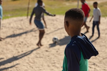 Boy looking at the kids playing football in the ground