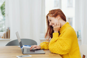 Young happy woman in yellow sweater using laptop