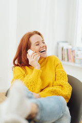 Redhead woman laughing as she chats on her phone
