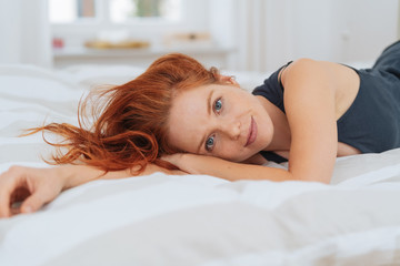 Young redhead woman relaxing on her bed