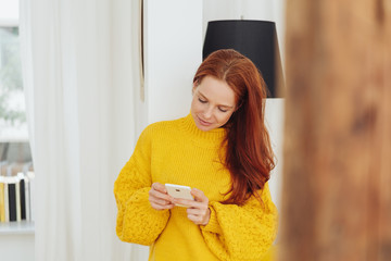 Trendy young woman reading a text message