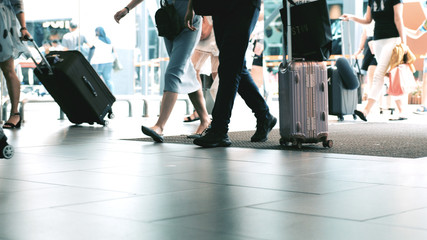 Travelers with baggages walking in terminal airport