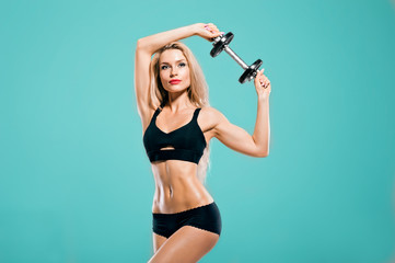 Sportive girl with an ideal figure posing in the studio with dumbbells in her hands.