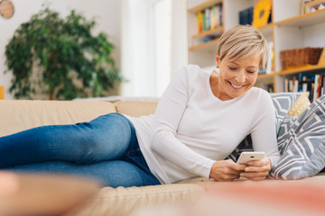 woman reclining on a sofa using a mobile