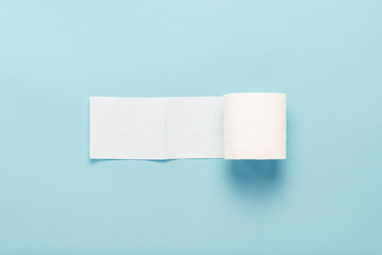 Roll of unfolded toilet paper on a blue background. Flat lay, top view