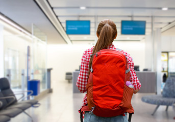travel, tourism and people concept - young woman with red backpack over airport terminal background