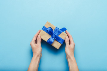 Female hands holding a gift with a blue ribbon on a blue background. Concept of a gift for the holidays, birthday, Christmas, wedding. Flat lay, top view
