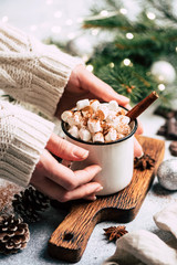 Christmas drink hot chocolate with marshmallows. Female hands holding mug of cozy hot chocolate with marshmallows and cinnamon over Christmas tree background