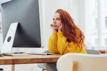 Bored young woman sitting working at a desktop