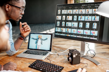 Two male photographers choosing woman's portraits at the working place with two computers in the studio