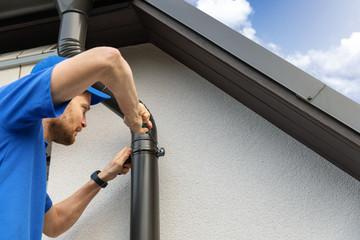 worker installing house roof gutter