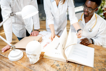 Phisicians studying with medical book and drawings on the table indoors. Close-up view focused on the book
