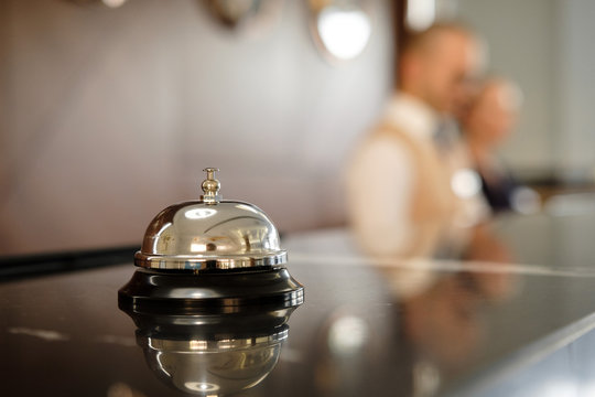 Modern luxury Hotel Reception Counter desk with Bell.  Service Bell locating at reception. Silver Call Bell on table, Receptionists on background. heck in hotel. Concept.