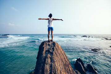 Freedom young woman outstretched arms on seaside rock cliff edge Wall mural