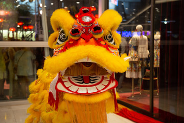 Chinese New Year lion dancing in yellow costume with mouth open. Traditional chinese dragon dance in a shopping mall in Bangkok, Thailand.