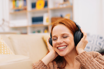 Woman in overhead headphones enjoying music