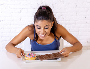 Portrait of young happy woman eating delighted chocolate bar and donuts