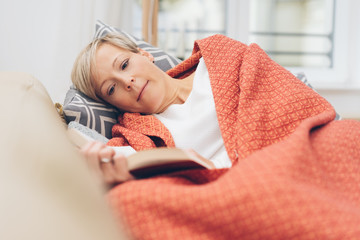 Mature blond woman lying reading a book