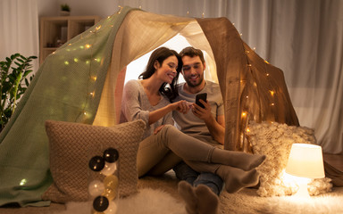 leisure, hygge, technology and people concept - happy couple with smartphone in kids tent at home