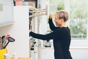 Woman opening the upper compartment of a fridge