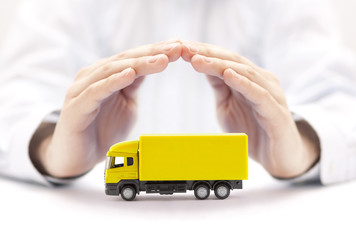 Car insurance. Yellow truck miniature covered by hands.