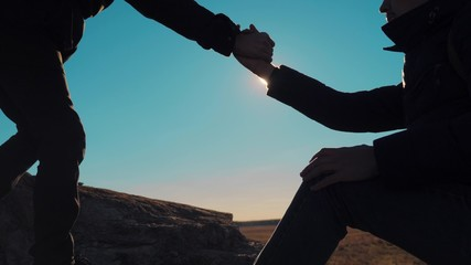 teamwork business travel trip. two men with backpacks hiking help each other silhouette in mountains with sunlight. slow motion video. teamwork friendship hiking help each other trust assistance the