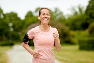 fitness, sport and healthy lifestyle concept - smiling woman with earphones wearing armband for smartphone, jogging at summer park and listening to music