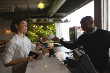 Waiter serving coffee to female executive at counter