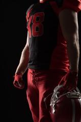 American football player standing with helmet against black
