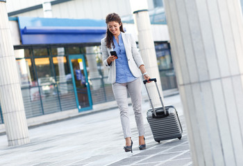 Young woman on business trip walking with her luggage and looking at phone at airport.