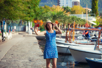 Young travelling woman in hat taking selfie photos over summer sunny mediterranean city with smartphone camera.