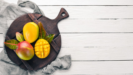 Mango. On a white wooden background. Tropical Fruits. Top view. Free copy space.