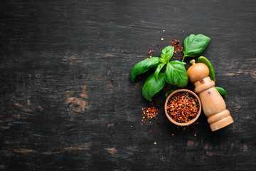 Fototapete - Fresh basil and spices. On a black wooden background. Top view. Free copy space.