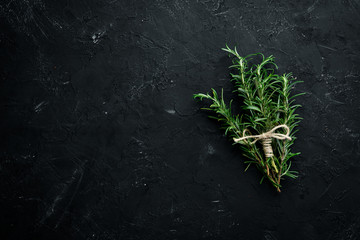 Wall Mural - Fresh green rosemary. On a black stone background. Top view. Free copy space.