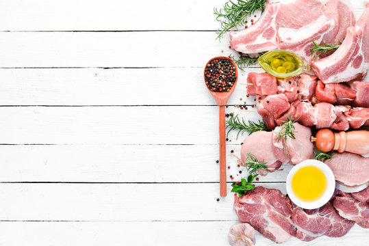 Raw meat for barbecue. Meat with spices and herbs. On a white wooden background. Top view. Free copy space.
