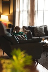 Woman using mobile phone on sofa in living room