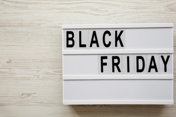'Black friday' word on lightbox over white wooden background, overhead view. Copy space.