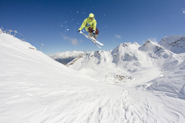Flying skier on snowy mountains. Extreme winter sport, alpine ski. Copy space.