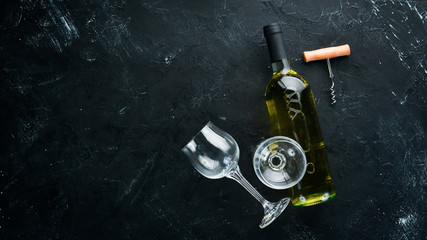 A bottle of white wine on a black stone background. Top view. Free copy space.