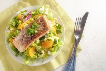 crispy fried salmon fillet on salad with tangerines, napkin and cutlery, bright background with copy space, high angle view from above