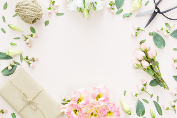 Flowers composition with gift on white pink background. Flat lay