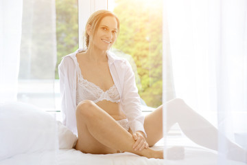 Young attractive woman in lingerie as underwear sits relaxed on bed