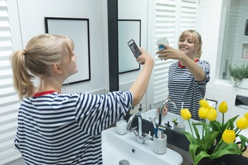 Woman taking selfie on mobile phone in bathroom