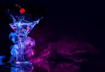 Poster Cocktail cherry falling into a martini splashing on blue and purple smoky background