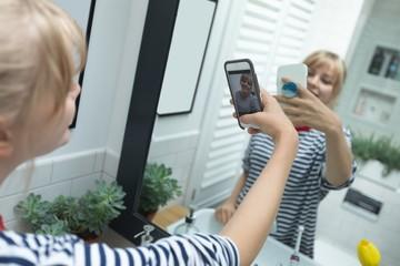 Woman taking selfie on mobile phone in bathroom