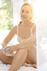 Young attractive woman in lingerie as underwear sits relaxed on bed and drinks coffee from a mug