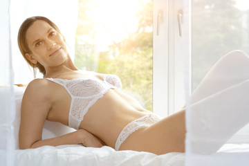 Young attractive woman in lingerie as underwear lies relaxed on bed